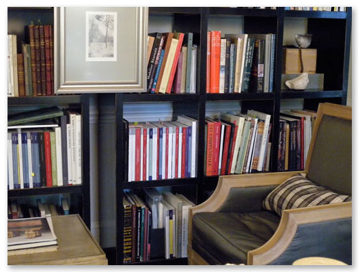 The bookcases on the west wall of the John Black's library are filled with international books about furniture, architecture, history, textiles, and biographies.